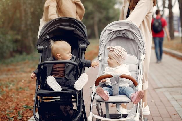 Due giovani madri che camminano in un parco in autunno con le carrozze Foto Gratuite