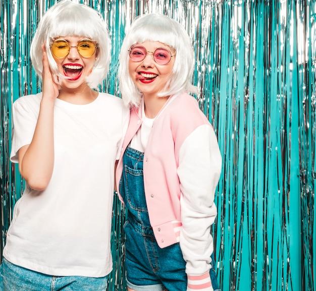 Due giovani ragazze sorridenti sexy dei pantaloni a vita bassa in parrucche bianche e labbra rosse le belle donne d'avanguardia di estate copre l'estate Foto Gratuite
