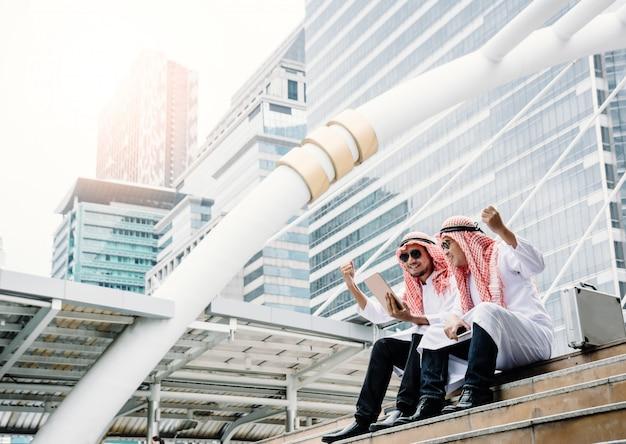 Due giovani uomini d'affari arabi stanno alzando le mani per esprimere la loro gratitudine per le trattative commerciali di successo e gli affari redditizi. Foto Premium