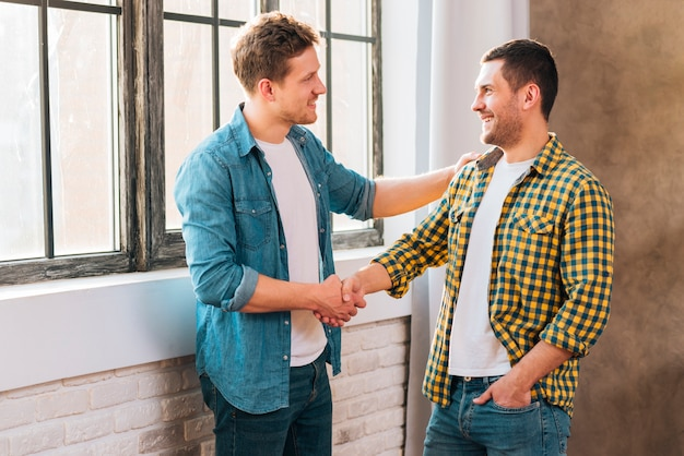 Due giovani uomini in piedi vicino alla finestra si stringono la mano Foto Gratuite