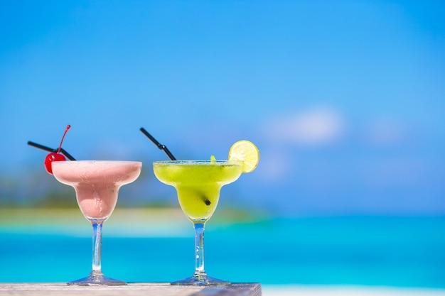 Due gustosi cocktail sulla spiaggia bianca tropicale Foto Premium