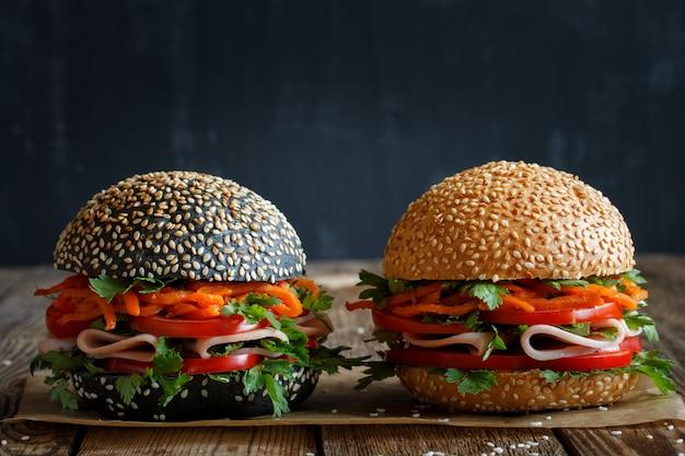 Due hamburger freschi appetitosi scuri e chiari con semi di sesamo, primo piano, con verdure fresche (pomodoro, peperone dolce), carote coreane, prezzemolo e prosciutto. nero sfocato. Foto Premium