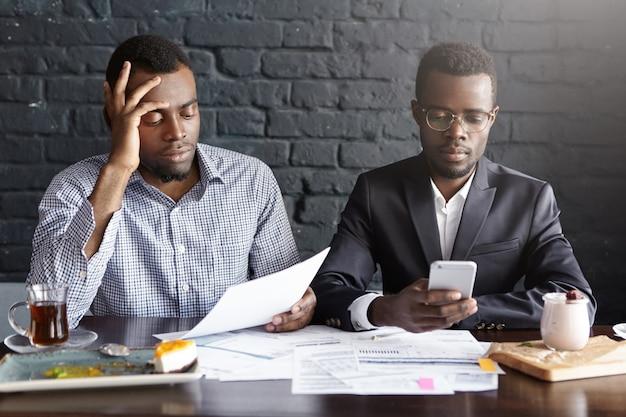 Due imprenditori dalla pelle scura seduti al tavolo del ristorante con le carte, preparati per un importante incontro di lavoro con potenziali partner, che sembrano concentrati. uomo con gli occhiali con il cellulare Foto Gratuite