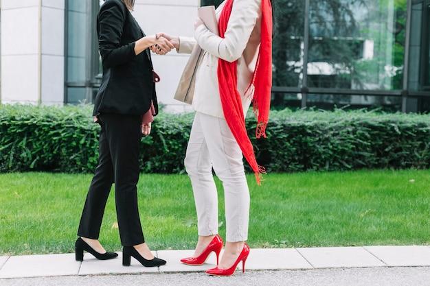 Due imprenditrice indossando tacchi alti agitando le mani Foto Gratuite