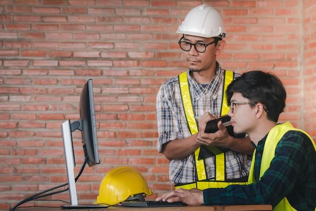 Due ingegneri e architetti asiatici stanno parlando di lavoro di informazione e attingendo da computer in progetti di architettura nei cantieri dei banchi. Foto Premium