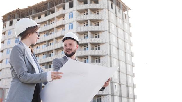 Due ingegneria sorridente professionale tenendo il modello e guardando a vicenda Foto Gratuite