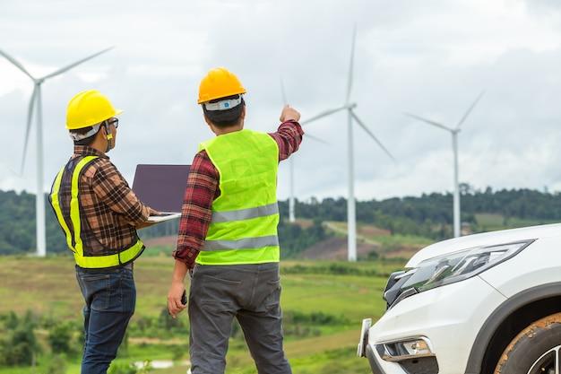Due ispezione e controllo dell'ingegnere del mulino a vento controllano la turbina eolica in cantiere utilizzando un'auto come veicolo. Foto Premium