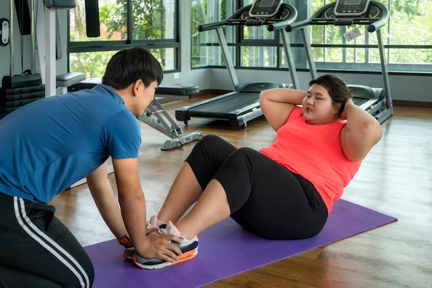 Due istruttori asiatici uomo e donna sovrappeso esercitano sedersi insieme in palestra moderna, felice e sorridere durante l'allenamento. le donne grasse si prendono cura della salute e vogliono perdere peso. Foto Premium
