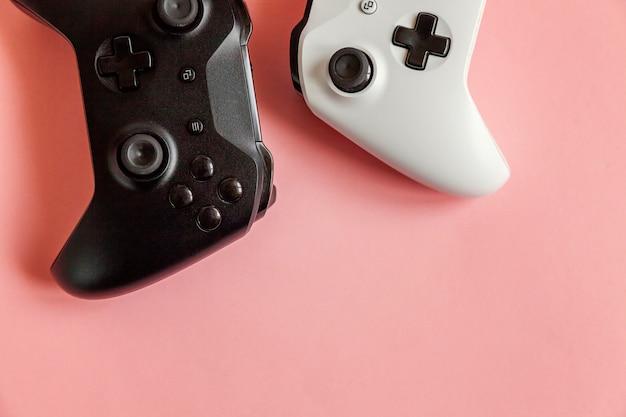 Due joystick bianco e nero su rosa Foto Premium