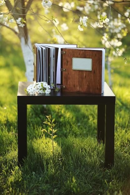 Due libri fotografici in legno sul tavolo nella natura. posto per l'iscrizione Foto Premium
