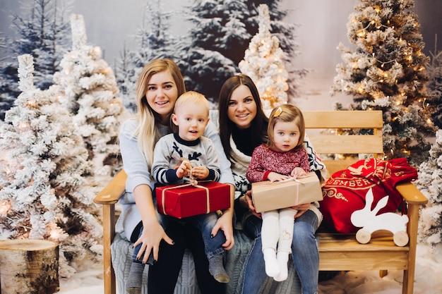 Due madri che si siedono con i bambini svegli e che tengono i regali di natale Foto Premium