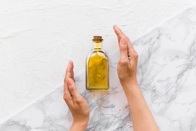 Due mani che coprono la bottiglia di olio d'oliva su due vivaci fondali Foto Gratuite