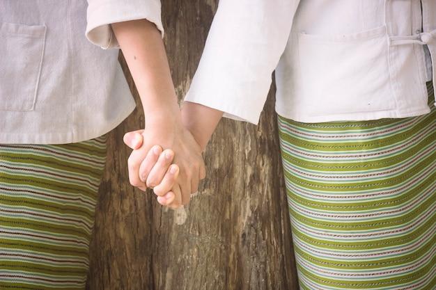 Due mani che tengono insieme. concetto di migliori amici. Foto Premium