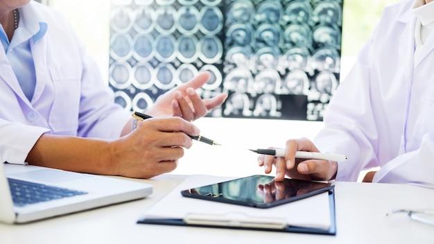 Due medici analizzano una scansione o un film a raggi x o spiega una scansione tc Foto Premium