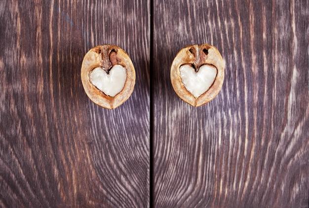 Due metà della noce a forma di cuore giacciono su due parti del tavolo di legno dipinto di scuro Foto Premium