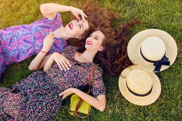 Due migliori amiche in abito boho colorato e capelli ricci che giacciono sull'erba verde Foto Gratuite