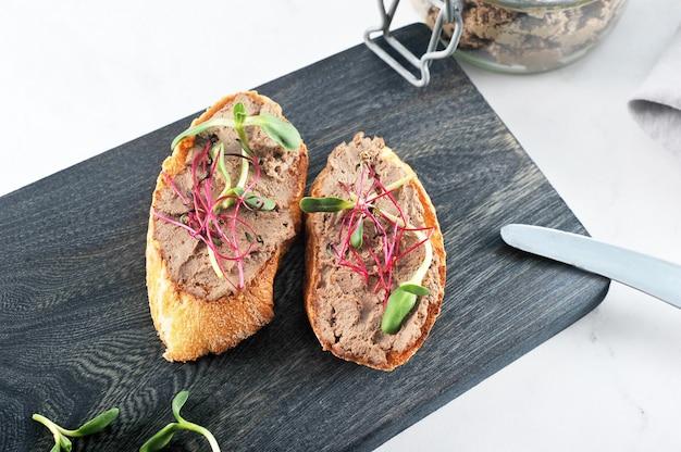 Due panini tostati di pane tostato con patè e verdure Foto Premium