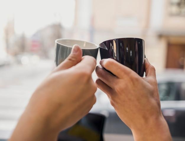 Due persone che bussano insieme alle tazze di caffè Foto Gratuite