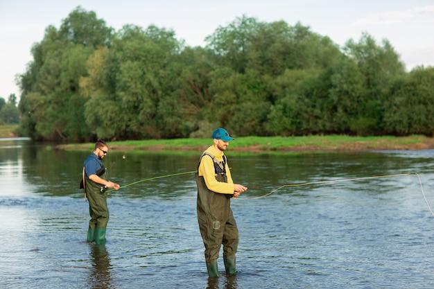 Due pescatori sono in piedi nel fiume con stivali di gomma Foto Premium