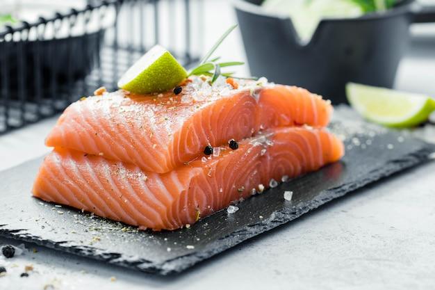 Due pezzi di filetto di salmone crudo con erbe fresche rosmarino, spezie e olio d'oliva su lastra di ardesia nera Foto Premium