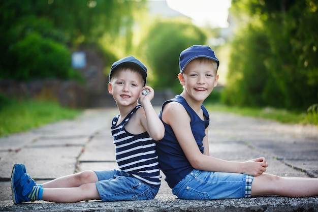 Due piccoli fratelli adorabili che si siedono sulla pietra il giorno di estate caldo e soleggiato. Foto Premium