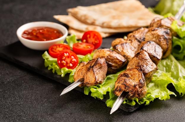 Due porzioni di shish kebab su un piatto di pietra con insalata. Foto Premium