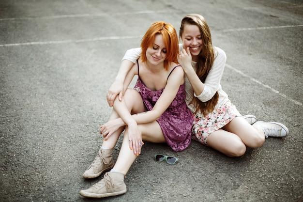 Due ragazze adolescenti seduti nel parco giochi Foto Premium