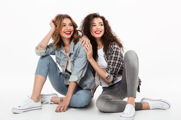 Due ragazze allegre che si siedono insieme sul pavimento e che distolgono lo sguardo sopra la parete bianca Foto Gratuite