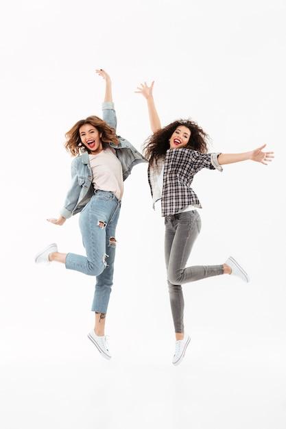 Due ragazze allegre integrali gioiscono e saltano sopra il muro bianco Foto Gratuite