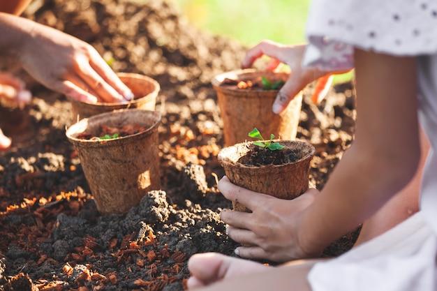 Due ragazze asiatiche del bambino che piantano le giovani piantine dentro riciclano insieme i vasi di fibra nel giardino Foto Premium