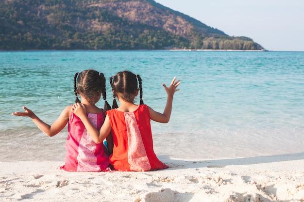 Due ragazze asiatiche sveglie del piccolo bambino che si siedono insieme e che giocano insieme sulla spiaggia Foto Premium