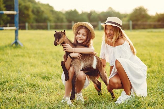 Due ragazze carine in un campo con capre Foto Gratuite