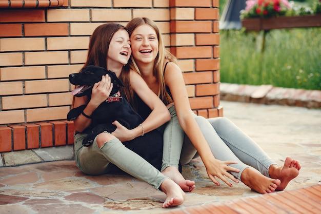 Due ragazze carine in un parco estivo con un cane Foto Gratuite