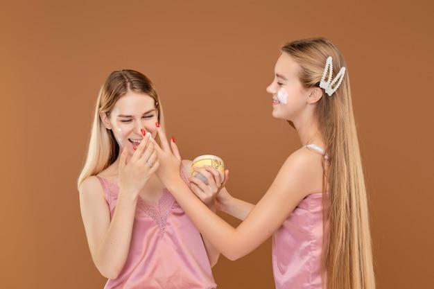 Due ragazze che applicano stupidamente faccia a faccia con la crema dell'acne Foto Premium