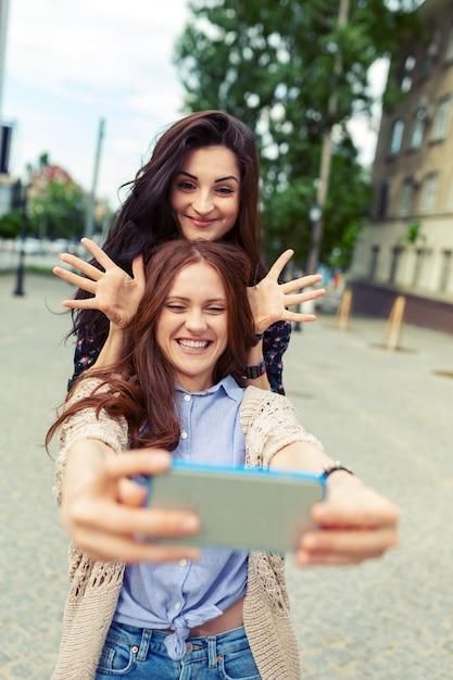 Due ragazze che fanno selfie divertenti per strada, divertendosi insieme Foto Gratuite