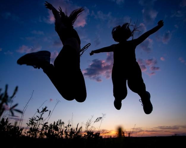 Due ragazze che saltano il cielo al tramonto al tramonto, ombre Foto Premium