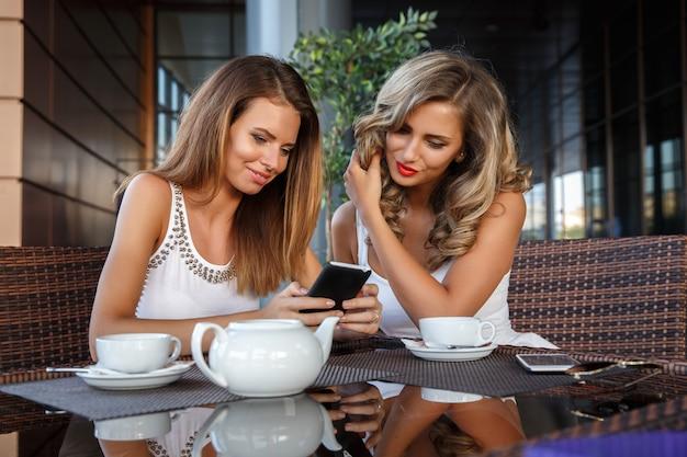 Due ragazze che si siedono al caffè Foto Premium