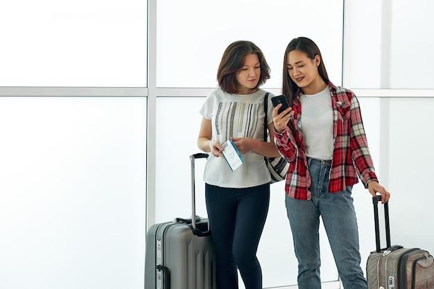 Due ragazze che utilizzano smartphone controllando il volo o il check-in online all'aeroporto, con i bagagli. concetto di tecnologia di viaggio aereo, vacanze estive o telefono cellulare Foto Premium