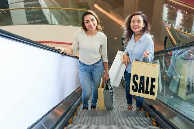 Due ragazze che vanno di sopra sulla scala mobile nel centro commerciale Foto Gratuite