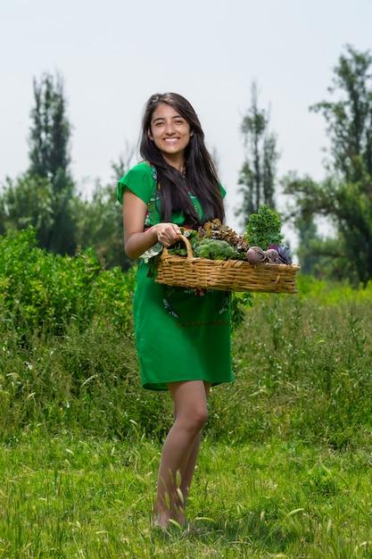 Due ragazze con un cesto di verdure in giardino Foto Premium