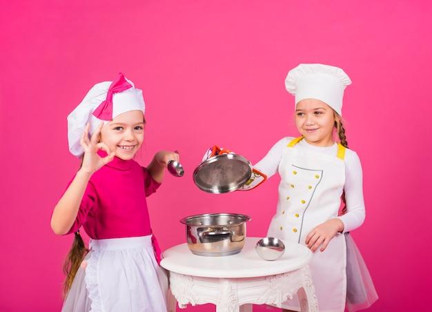 Due ragazze cuochi con la pentola che mostra gesto giusto Foto Gratuite