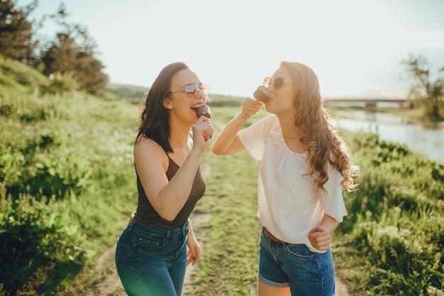 Due ragazze felici, che mangiano il gelato, il calore estivo e il divertimento, con gli occhiali, in camicia bianca e nera. al tramonto, espressione facciale positiva, all'aperto Foto Premium