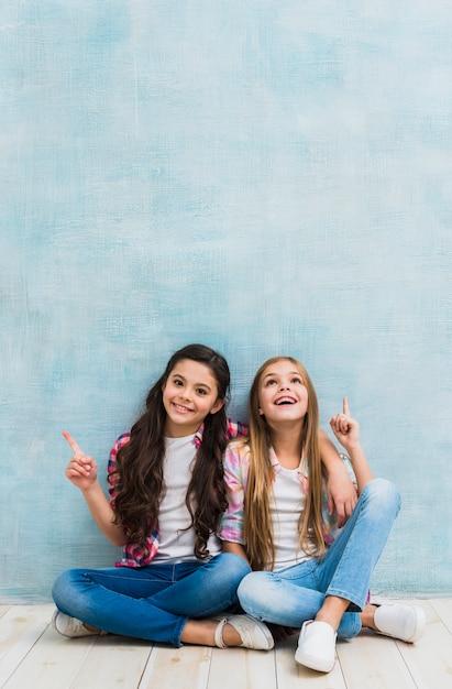 Due ragazze felici che si siedono davanti alla parete blu che indica la loro barretta verso l'alto Foto Gratuite