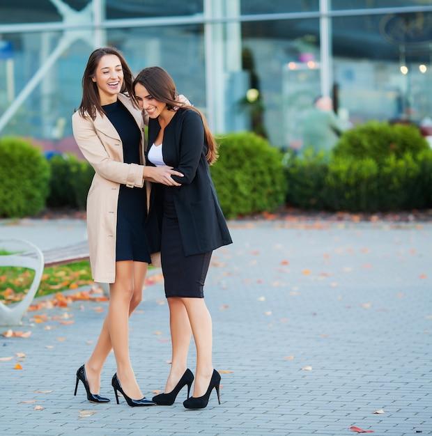 Due ragazze felici che viaggiano insieme all'estero, portando i bagagli in valigia in aeroporto Foto Premium