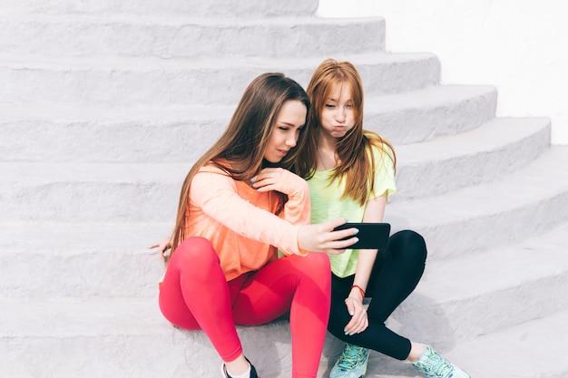 Due ragazze in abbigliamento sportivo scattare foto di se stessi su un telefono cellulare e ridendo Foto Premium