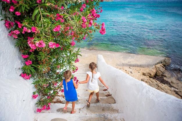 Due ragazze in abiti blu divertirsi all'aperto. bambini alla strada del tipico villaggio tradizionale greco con pareti bianche e porte colorate sull'isola di mykonos, in grecia Foto Premium