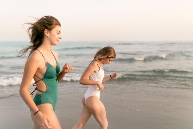 Due Ragazze In Bikini Che Camminano Vicino Al Mare In Spiaggia