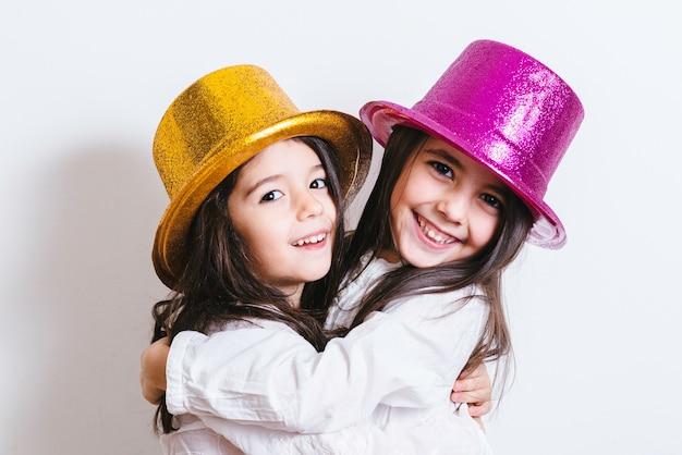 Due ragazze in posa con cappelli lucidi gialli e rosa Foto Premium