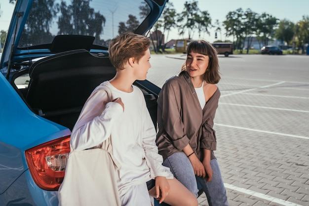 Due ragazze nel parcheggio del bagagliaio aperto Foto Gratuite