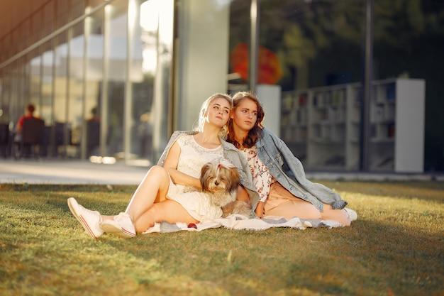 Due ragazze seduti in un parco con un cagnolino Foto Gratuite